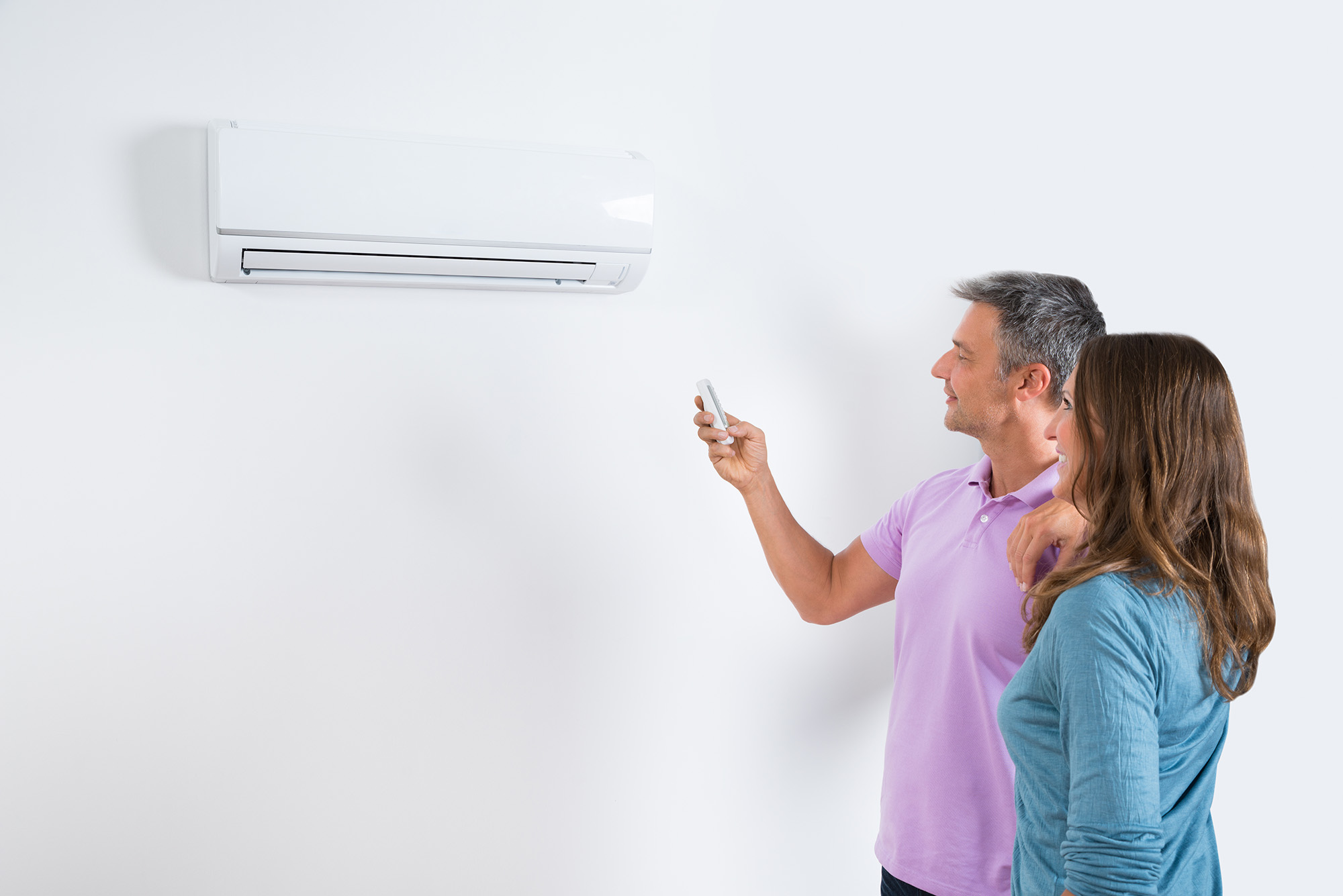 Mature Couple Standing In Front Of Air Conditioner And Adjusting The Temperature By Remote